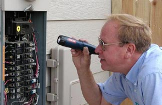 man in blue shirt inspecting a circuit breaker